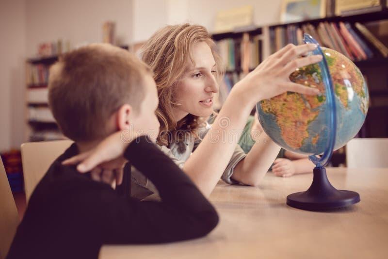 Bildung und Spaß Kinder mit dem Lehrer, der Spiele im Klassenzimmer spielt stockbild