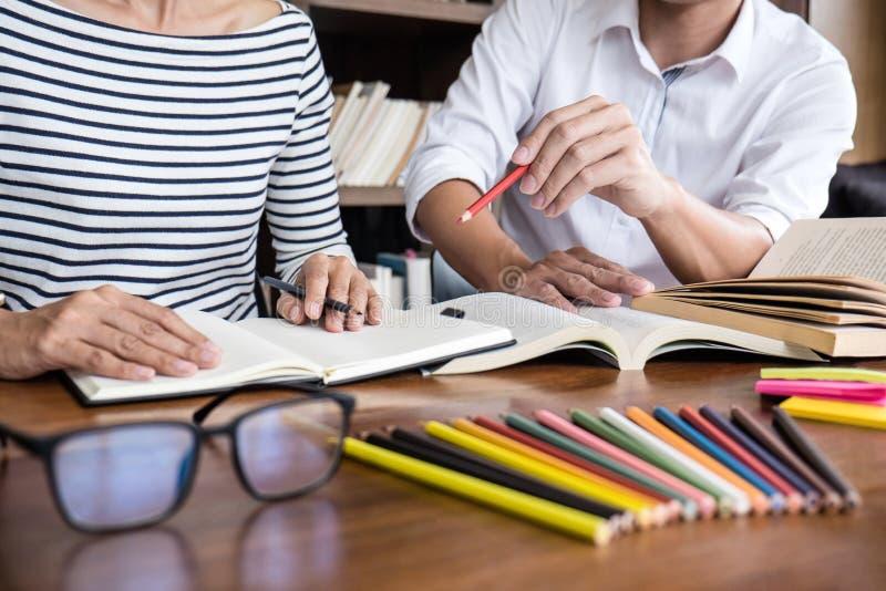Bildung, Unterricht, Lernkonzept Zwei hohe Sch?ler- oder Mitsch?lergruppe, die in der Bibliothek mit dem Hilfsfreundhandeln sitzt lizenzfreie stockbilder