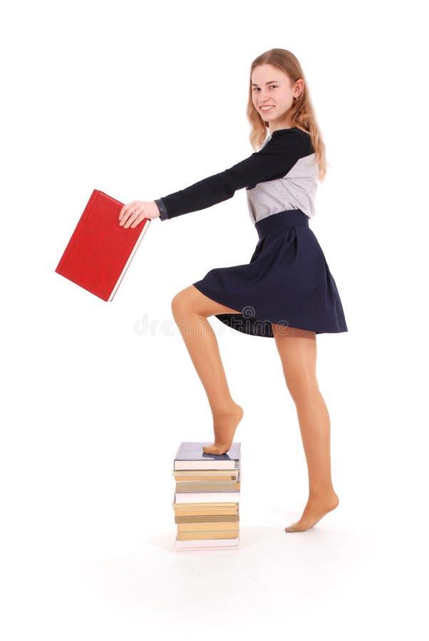 Bildungs-, Leute-, Jugendlich- und Schulkonzept - Jugendlichschulmädchen, das auf Stapel Büchern steht lizenzfreie stockfotografie