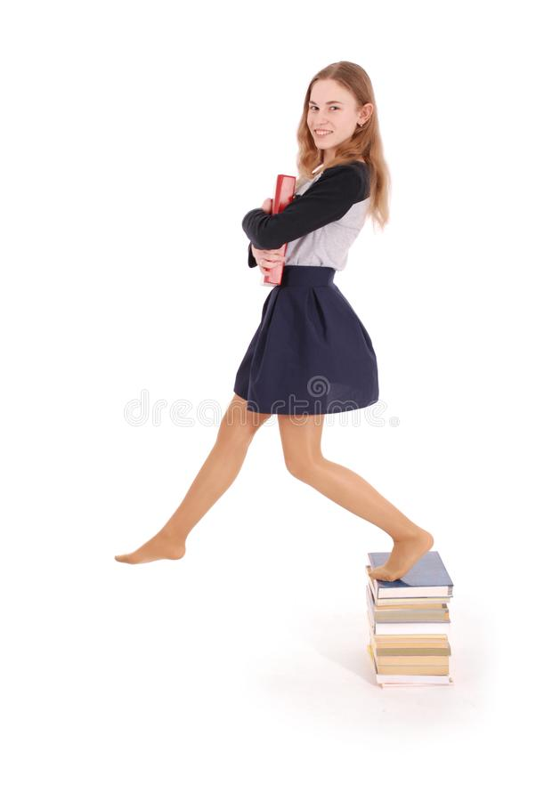 Bildungs-, Leute-, Jugendlich- und Schulkonzept - Jugendlichschulmädchen, das auf Stapel Büchern steht stockfotos