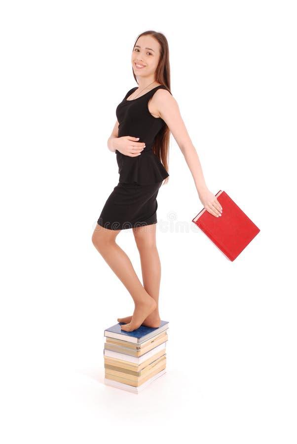 Bildungs-, Leute-, Jugendlich- und Schulkonzept - Jugendlichschulmädchen, das auf Stapel Büchern steht stockbilder
