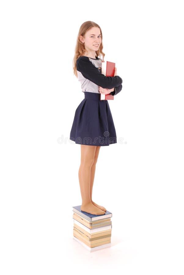 Bildungs-, Leute-, Jugendlich- und Schulkonzept - Jugendlichschulmädchen, das auf Stapel Büchern steht lizenzfreies stockbild