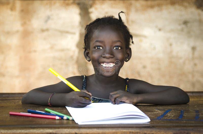 Bildungs-Symbol: Großes Toothy Lächeln auf afrikanischem Schulmädchen schlucht stockfotografie