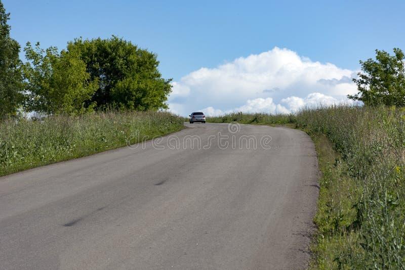Bilen går på asfaltvägen, bland gräs, träd royaltyfri bild