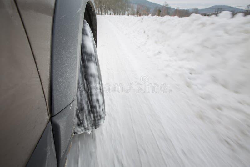 Bilen med vinter tröttar på en hal snöig väg royaltyfria bilder