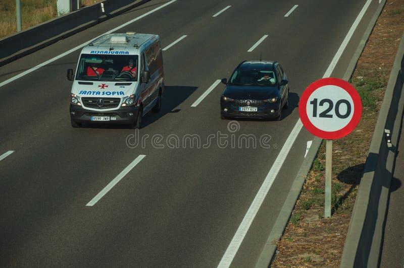 Bilen och ambulansen på huvudvägen och HASTIGHETSBEGRÄNSNING undertecknar in Madrid royaltyfri fotografi