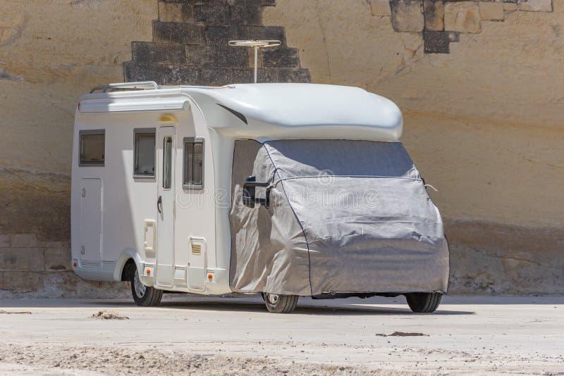 Bilen släp skåpbil motorhome som parkeras i parkeringsplatsen, kabinen, täckas med en markis royaltyfri bild
