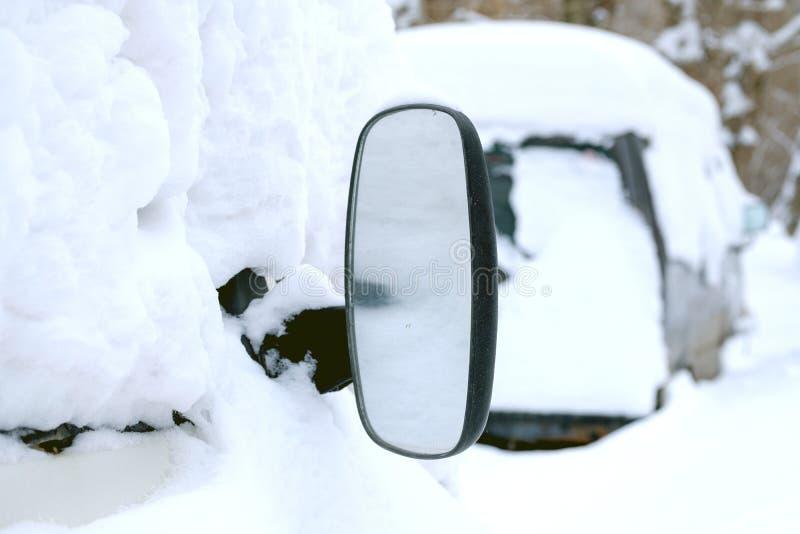 Bilen täckas med snö klibbar ut en stor spegel, mycket snö fotografering för bildbyråer