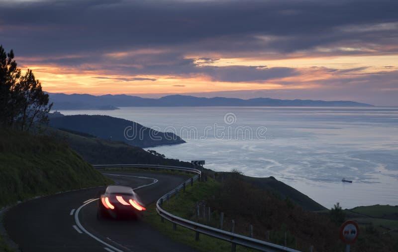 Bilen tänder i vägen, baskisk kust fotografering för bildbyråer