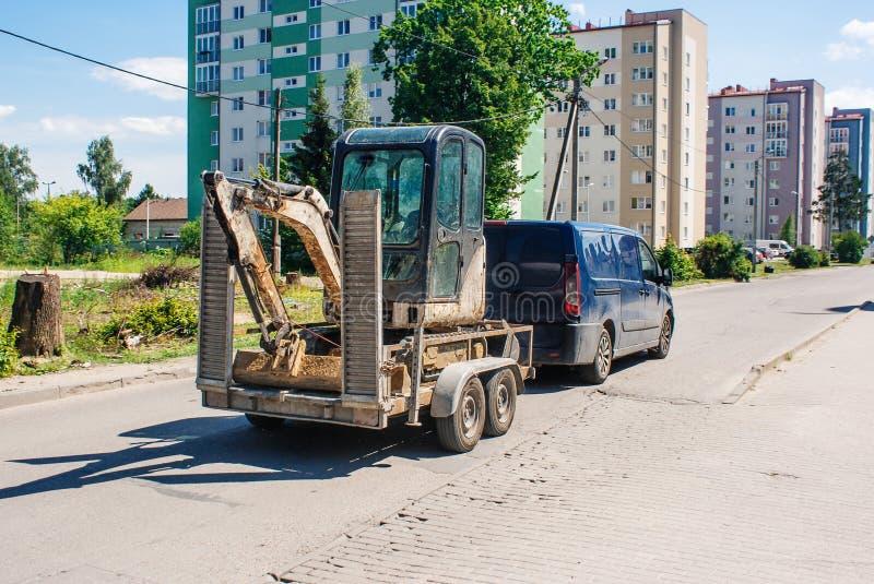 Bilen transporterar en mini- grävskopa som laddas på en släp royaltyfri fotografi