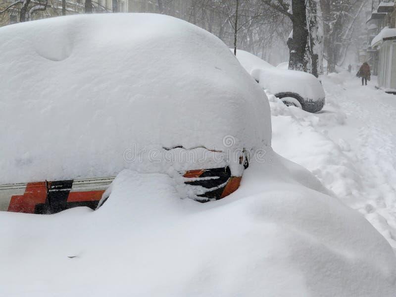 Bilen under snö, naturkatastrofer övervintrar, häftiga snöstormen, tung snö paralyserade staden, kollaps Snö täckte cyklon Europa royaltyfria foton