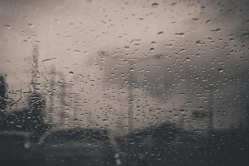 Bilfönstret med regn tappar på exponeringsglas eller vindrutan, suddig trafik på regnig dag i staden fotografering för bildbyråer