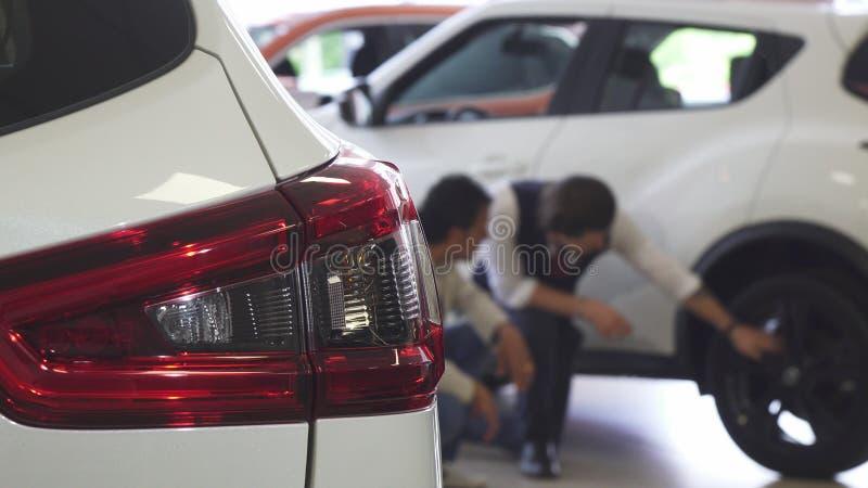 Bilförsäljare och hans manliga klient som diskuterar gummihjul av en till salu bil royaltyfria bilder