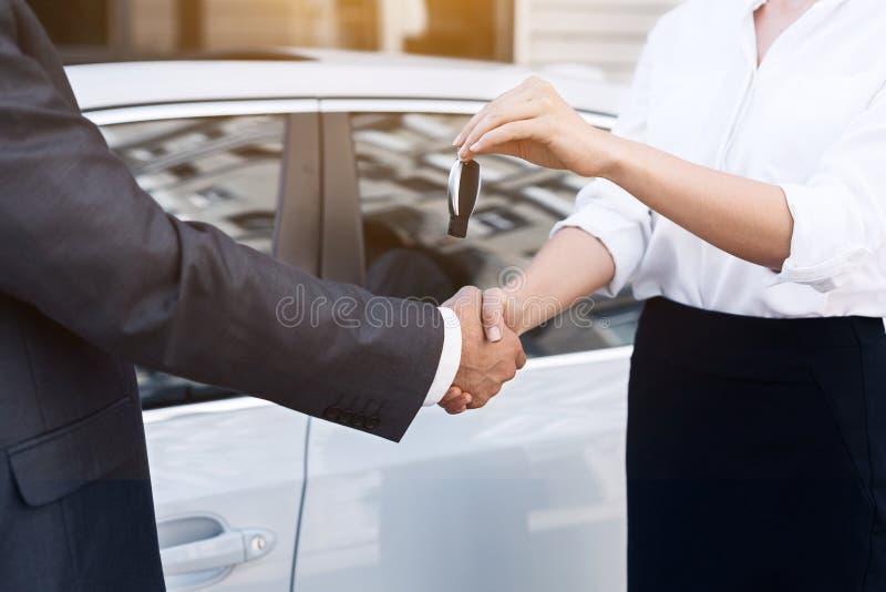 Bilförsäljare som ger tangent till nya ägaren royaltyfria foton
