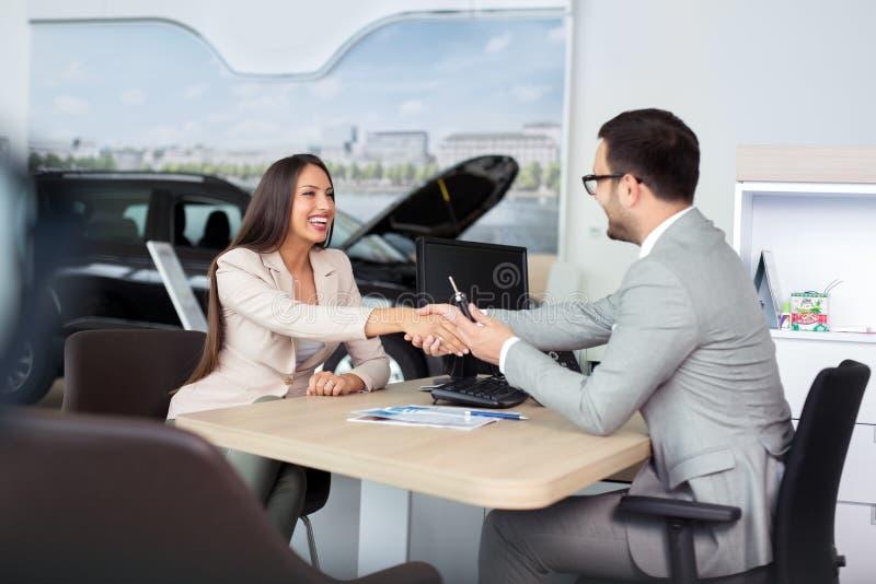Bilförsäljare som ger tangenten av den nya bilen till den unga attraktiva flickan royaltyfri bild