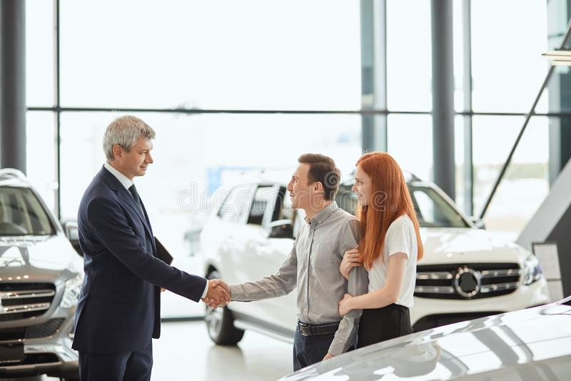 Bilförsäljningschef som berättar om särdragen av bilen till kunderna på återförsäljaren royaltyfri bild