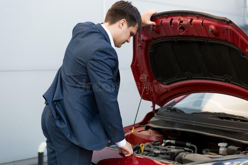 Bilförsäljningschef som ser under hättan av bilen arkivfoto