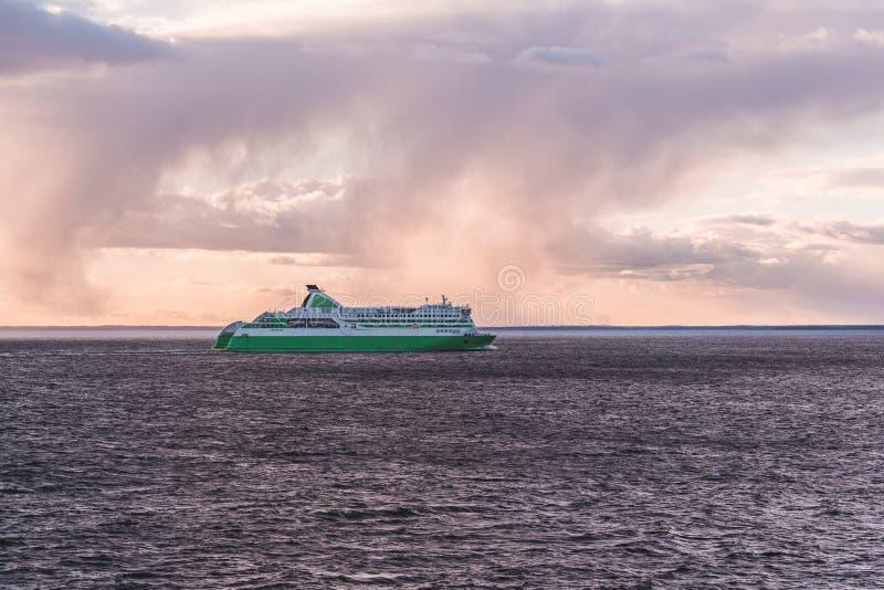 Bilf?rja p? dess v?g fr?n Tallinn till Helsingfors p? en afton med solnedg?ng och moln arkivfoton