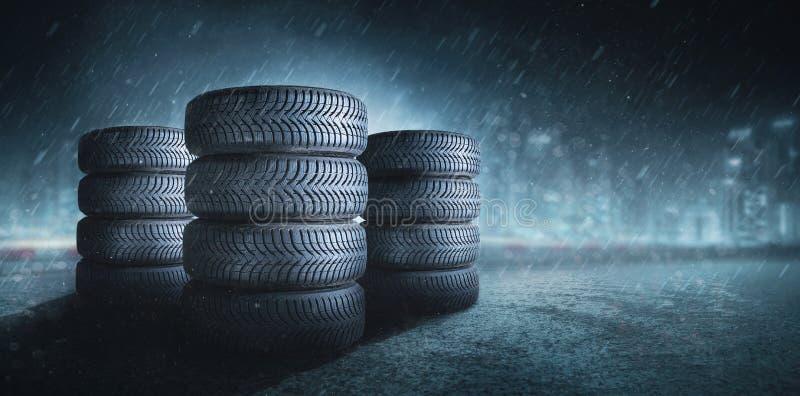Bilgummihjul på en regnväg arkivfoto