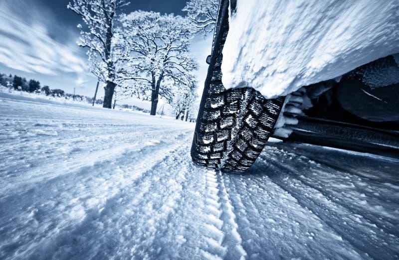 Bilgummihjul på vintervägen royaltyfria foton