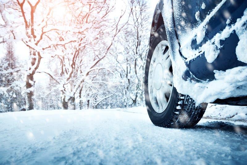 Bilgummihjul på vintervägen arkivfoto