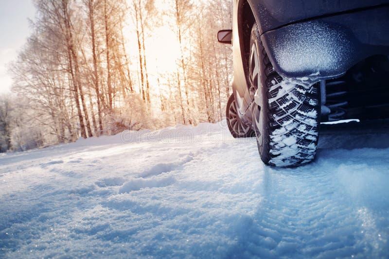 Bilgummihjul på vintervägen som täckas med snö arkivbild