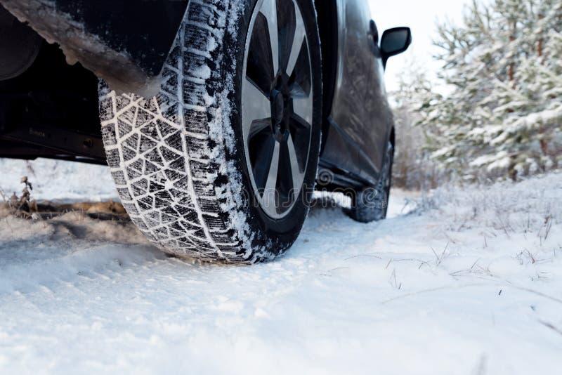 Bilgummihjul på vintervägen som täckas med snö Medel på snöig väg arkivfoto