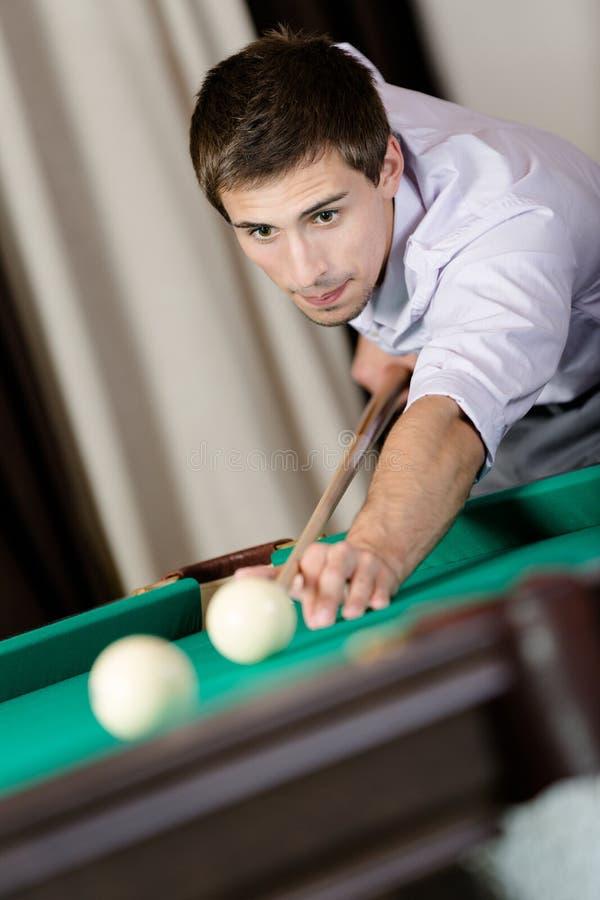 Homem que joga bilhar no clube de jogo fotografia de stock
