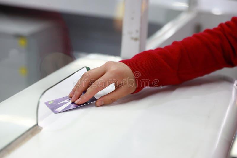 Bilhete da inserção do cartão do tráfego da mão da mulher ao estação de caminhos-de-ferro da entrada do bilhete fotografia de stock royalty free