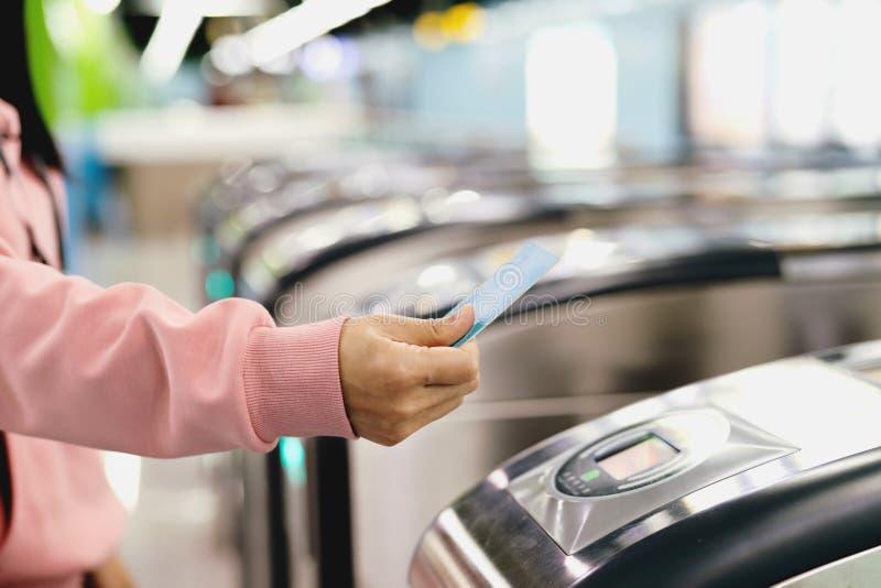 Bilhete de trem da exploração da mão da mulher à porta da entrada do metro Conceito do transporte imagem de stock