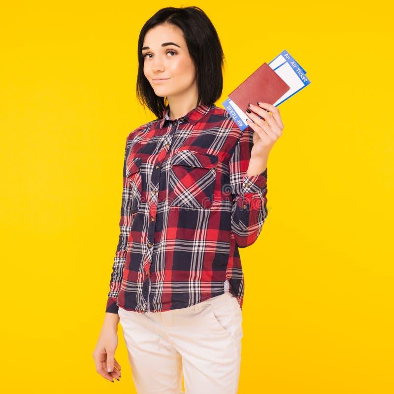 Bilhete entusiasmado de sorriso novo da passagem de embarque do passaporte da terra arrendada do estudante de mulher no fundo ama fotografia de stock