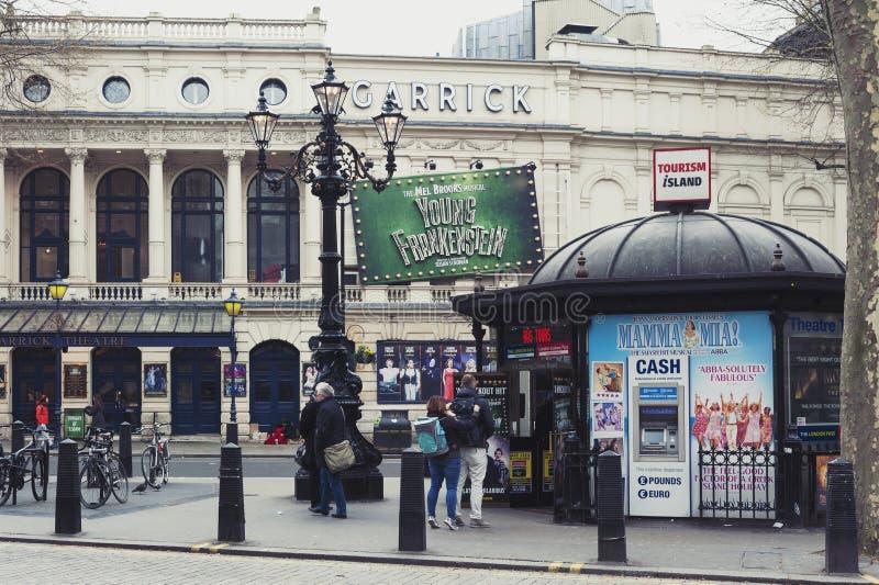 A bilheteira e a cabine de informações turísticas da ilha do turismo em Charing cruzam a estrada com Garrick Theatre visível no f imagem de stock royalty free