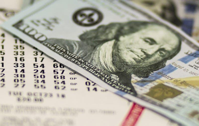 Bilhetes de loto com cem notas de dólar imagens de stock royalty free