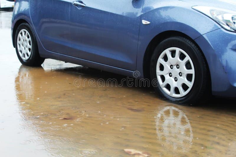 Bilhjul in en pöl av regnvatten, regndroppar och vattencirklar Vinterväder i Israel: regn, pölar, floder och översvämning arkivfoto