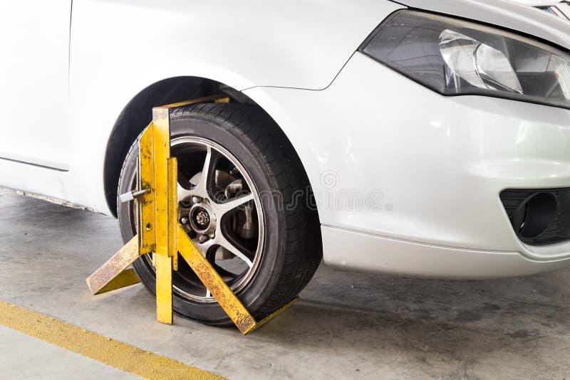 Bilhjul som klämmas fast för olaglig parkeringskränkning på parkeringshuset royaltyfri fotografi