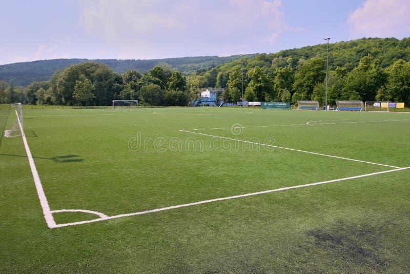 Bilina Tjeckien - Maj 12, 2018: stort gräs- fotbollfält mellan träd i vår royaltyfri bild