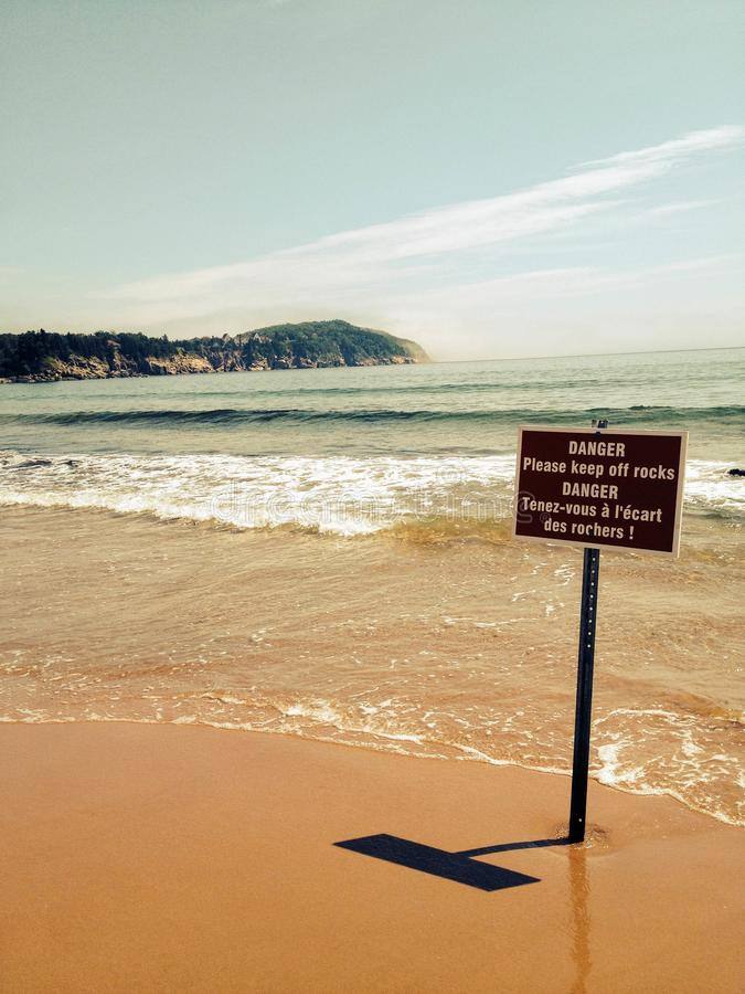 A bilingual `beware of rocks` sign posted on the sandy beaches o royalty free stock image