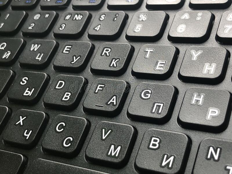 QWERTY keyboard black. Bilingual QWERTY English and Russian alphabet black keyboard stock photo