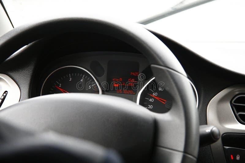 Bilinre med en chaufför, en bilinstrumentbräda och en styrning arkivbild