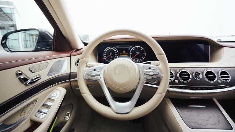 Bilinrelyx Inre av den moderna bilen för prestige Piska det bekväma plats-, instrumentbräda- och styrninghjulet vitt arkivbilder