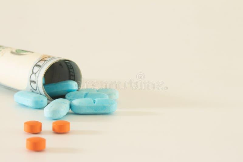 biljet van 100 dollar dat is verrekend met legale medicijnen die pillen of gekleurde medicijnen worden genoemd op een witte neutra stock afbeeldingen