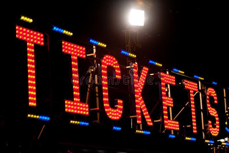Biljettneon undertecknar in natten arkivbild