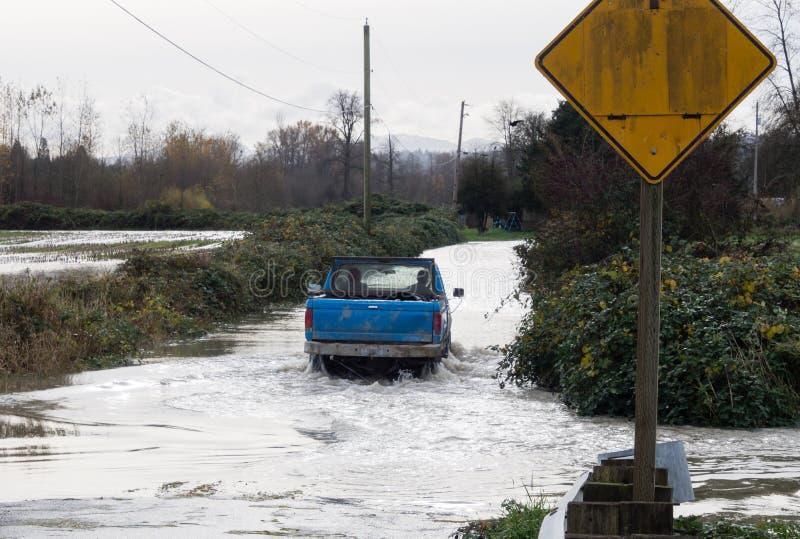 Bilkörning på den översvämmade vägen royaltyfri fotografi