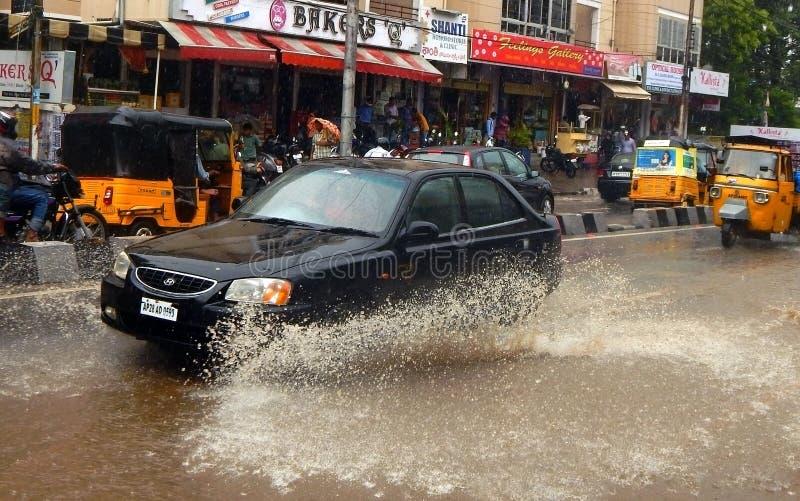 Bilkörning på en översvämmad väg under en flod som orsakas av hällregn arkivfoton