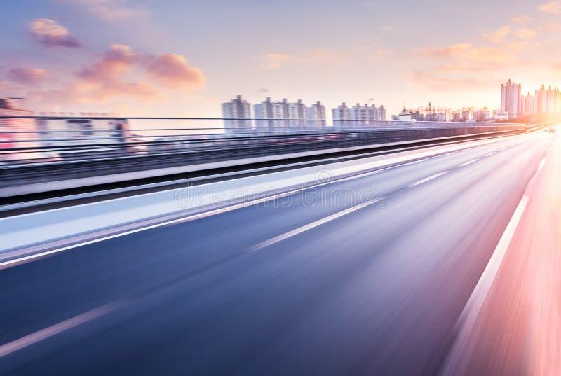 Bilkörning på motorväg på solnedgången, rörelsesuddighet royaltyfri foto