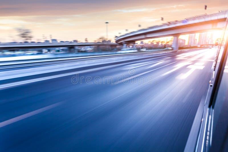 Bilkörning på motorväg på solnedgången, rörelsesuddighet arkivbild