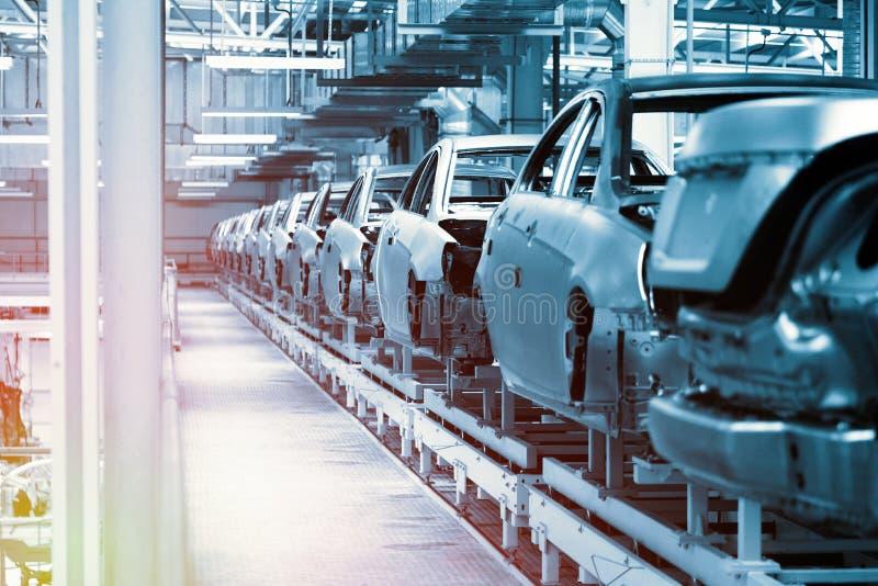 Bilkroppar är på monteringsband Fabrik för produktion av bilar i blått Modern bilindustri Blått tonar arkivbild
