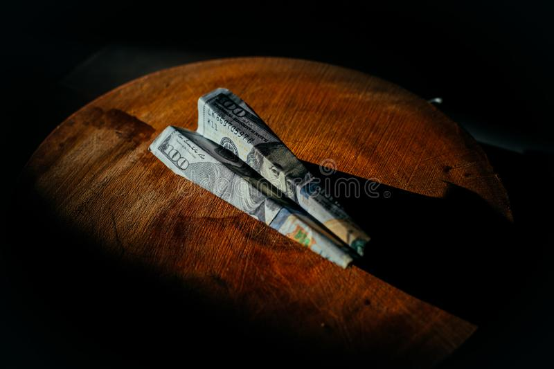 $ 100 bill in the form of an airplane lying on a wooden circle. the plane is made from banknotes stock photos