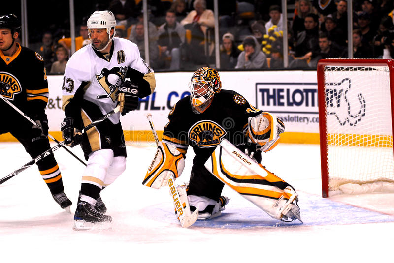 Bill Guerin and Tim Thomas. Tim Thomas of the Boston Bruins and Bill Guerin of the Pittsburgh Penguins battle for position in the Bruins zone stock photo