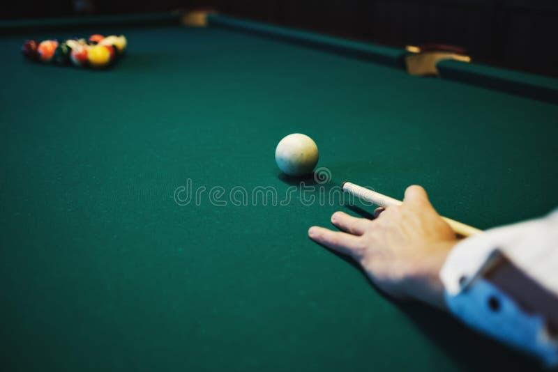 Billar americano Hombre que juega el billar, billar Jugador que se prepara para tirar, golpeando la bola de señal foto de archivo